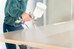 Staining wood with spray gun. Close up worker`s hand with spray gun applying paint on timber, wood coloring royalty free stock photos