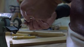 Close-up of a worker's hands grinding a chisel on a grinding stone in a workshop. 4k. 4k video. slow motion. 24 fps.  stock footage