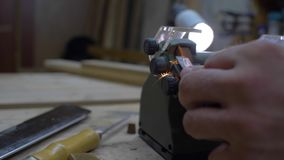 Close-up, worker sharpening a chisel on a grindstone, sparks beautifully fly out from under the stone. 4k. 4k video. slow motion. 24 fps stock footage