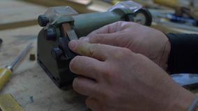 Close-up, worker sharpening a chisel on a grindstone, sparks beautifully fly out from under the stone. 4k. 4k video. slow motion. 24 fps stock video