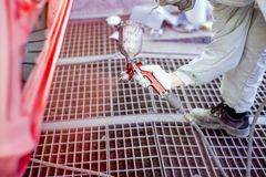 Close-up of worker spraying red paint on body of a car Royalty Free Stock Photos