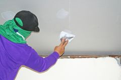 Worker using plaster gypsum on putty knife at ceiling royalty free stock photo