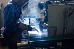 Close-up of a worker wearing a full protective gear. With mask and gloves and a rubber apron, welding together two pieces of an exhaust pipe stock photos