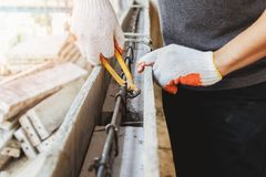Close up of workers hands using pincers bind steel wire to rebar. Before concrete is poured over it royalty free stock photography