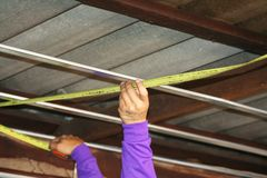 Workers measuring wood under roof, prepare for ceiling installation royalty free stock photo