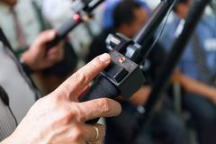 Close-up of working camera of man hand, operator at work. in the hall full of people. Stock photo Stock Image