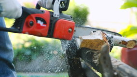 Close-up of working with chainsaw. Close-up of unrecognizable man using chainsaw to sawn a birch log stock footage