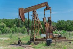 Working pump jack pumping crude oil at oil drilling site in rural USA royalty free stock image