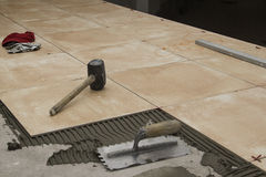 Close up of a workman's tools on a floor that is being tiled. Stock Photo