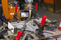 Close up workpieces and jig fixture with manual quick clamp for electric mig robot welding process at factory.  royalty free stock image