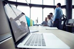 Close-up of workplace in modern office with business people behind. Colleagues meeting to discuss their future financial stock image