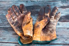 Close up of worn leather work gloves on wood background, stained with grease and industrial oil royalty free stock image