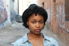 Close up of worried Black woman on isolated dirty alley with graffiti background stock images