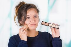 Close up of worried young woman holding a make up palette and doing crazy make-up in her face using a sponge, in a Royalty Free Stock Images