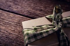 Wrapped gift box on wooden plank Stock Photos