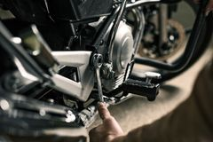Close up of wrench near motorcycle. Man`s hand with wrench fixing motorcycle in garage. Low key picture Stock Photo