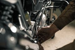 Close up of wrench near motorcycle. Man`s hand with wrench fixing motorcycle in garage. Low key picture Royalty Free Stock Image