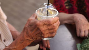 Close-up wrinkled hand of the man with lemonade. stock footage