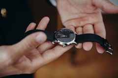 Man holding a watch in the hands before to put it on. Royalty Free Stock Photo