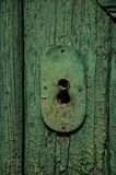 Close-up of wrought iron keyhole in an old wooden worn door royalty free stock photography