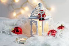 Close up of Xmas lantern with candles and red cozy balls. Christmas decoration on white fur. Shallow depth of field and bokeh. Stock Images