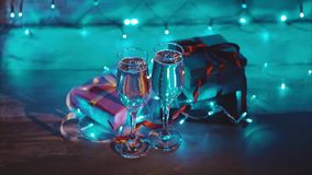 Close up of xmas and new year presents and two glasses of bubbling champagne. Close up shot of christmas and new year gift boxes and two glasses of bubbling stock video footage