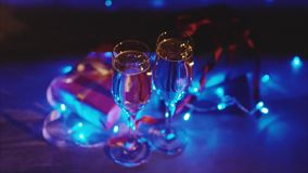 Close up of xmas and new year presents, two glasses champagne with blue garland. Close up shot of christmas and new year gift boxes and two glasses of bubbling stock video