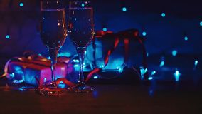 Close up of xmas and new year presents, two glasses champagne with blue garland. Close up shot of christmas and new year gift boxes and two glasses of bubbling stock video footage