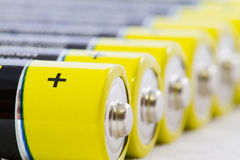 Close-up of yellow black AAA alkaline batteries isolated on whit. Close-up of a diagonal row of yellow black AAA alkaline batteries isolated on a white Royalty Free Stock Photo