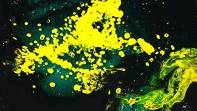 Close-up of yellow and blue paint stains mixing with dark surface. Color creation and art concept. Close-up of yellow and blue paint stains mixing with dark stock video