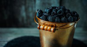 Close up yellow brass bucket with berry of blackberry stand on black stone stand on wood board. Close up yellow brass bucket with berry of blackberry stand on stock image