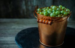 Close up yellow brass bucket with berry of green gooseberry. Which stand in right side on black stone stand on wood background. Close up yellow brass bucket with stock images