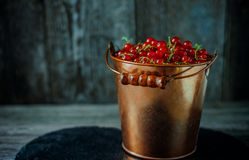 Close up yellow brass bucket with berry of red currant. Which stand on black stone in right side stand on wood background. Close up yellow brass bucket with royalty free stock photos