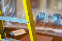 Free Close Up. Yellow Construction Ladder. Blurred Plastic Drop Cloth Hangs From Ceiling To Floor In Background Stock Photo - 170985460