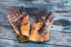 Close up of yellow dirty work gloves on a wooden table stained with grease and oil. Yellow dirty work gloves on a wooden table stained with grease and oil royalty free stock image