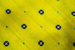 Yellow fabric texture. A close up of a Yellow fabric with lines and blue dots stitching Royalty Free Stock Image
