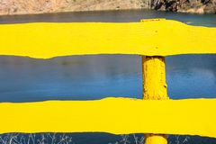 Close-up yellow fence on backdrop of lake stock photo