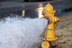 Close-up of yellow fire hydrant gushing water across a street with wet highway and tire from passing car behind.  stock photography
