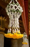 Close up of yellow flowers hanging from the roof of a pagoda. Stock Photo