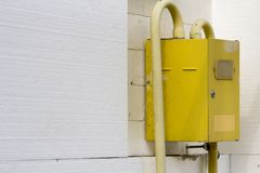 Close-up of yellow gas meter box with connecting pipes hanging on the corner of house wall insulated with white rigid polyurethane. Styrophome sheets stock images