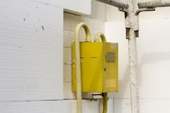 Close-up of yellow gas meter box with connecting pipes hanging o. N the corner of house wall insulated with white rigid polyurethane styrophome sheets royalty free stock image