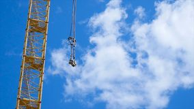 Close up of a yellow and green crane boom with main block and jib against a clear blue sky. Tower building cranes Royalty Free Stock Photography