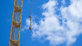 Close up of a yellow and green crane boom with main block and jib against a clear blue sky. Tower building cranes Stock Photography