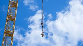 Close up of a yellow and green crane boom with main block and jib against a clear blue sky. Tower building cranes Royalty Free Stock Image