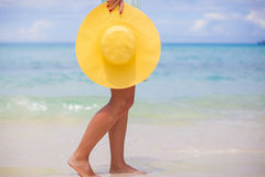 Close up of yellow hat at female hands on beach royalty free stock photos