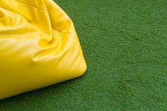 Yellow leather bean bag chair. Close up of yellow leather bean bag chair on the artificial grass royalty free stock image