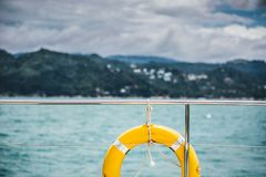 Close-up Yellow life ring hanging on boat with ocean background. stock photography
