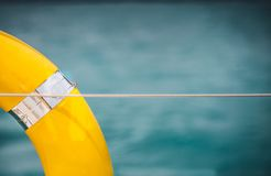 Close-up Yellow life ring hanging on boat with ocean background. stock photos