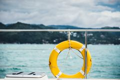 Close-up Yellow life ring hanging on boat with ocean background. Close-up Yellow life ring hanging on boat with ocean background stock images