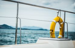 Close-up Yellow life ring hanging on boat with ocean background. stock images